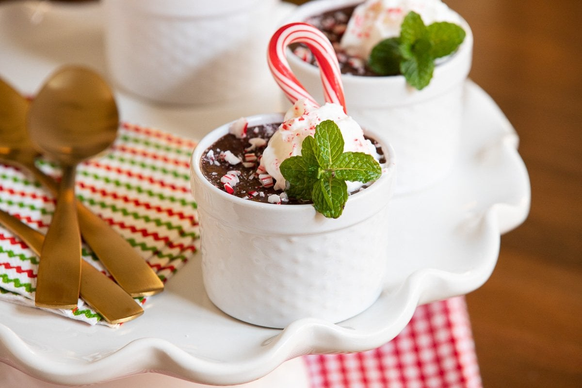 Horizontal closeup photo of cups of Ridiculously Easy Chocolate Peppermint Pots de Crème on a white scalloped serving plate. The cups are garnished with candy canes, fresh mint leaves and whipped cream.