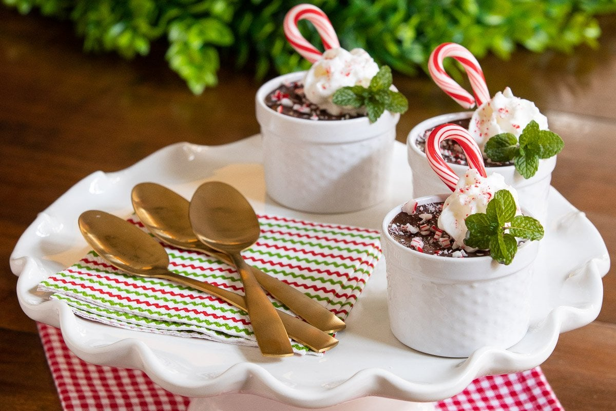 Horizontal photo of cups of Ridiculously Easy Chocolate Peppermint Pots de Crème on a white scalloped serving plate garnished with candy canes, mint and whipped cream.