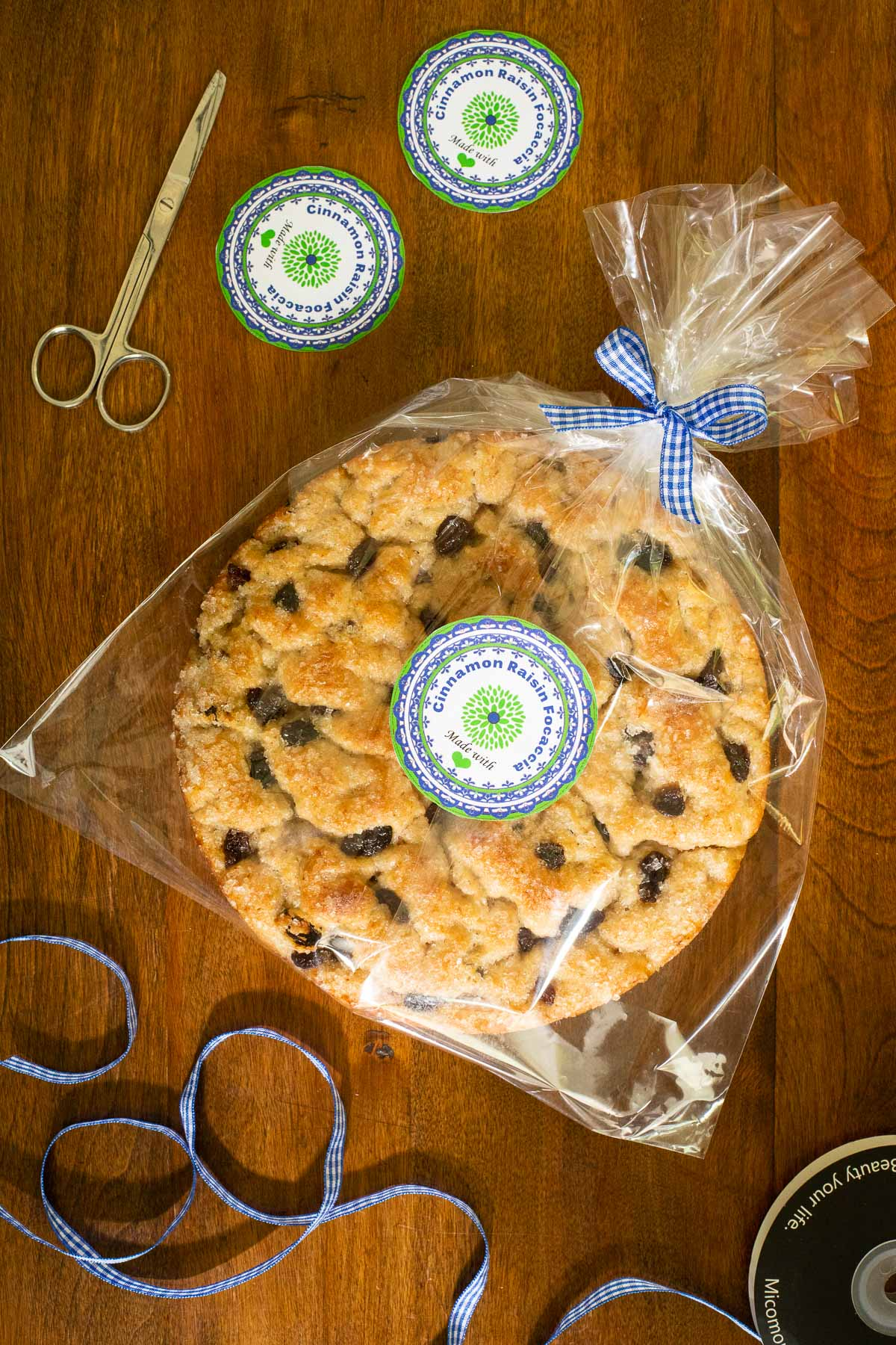 Vertical overhead photo of a loaf of Ridiculously Easy Cinnamon Raisin Focaccia bread in a clear plastic wrap with a custom gift label attached.