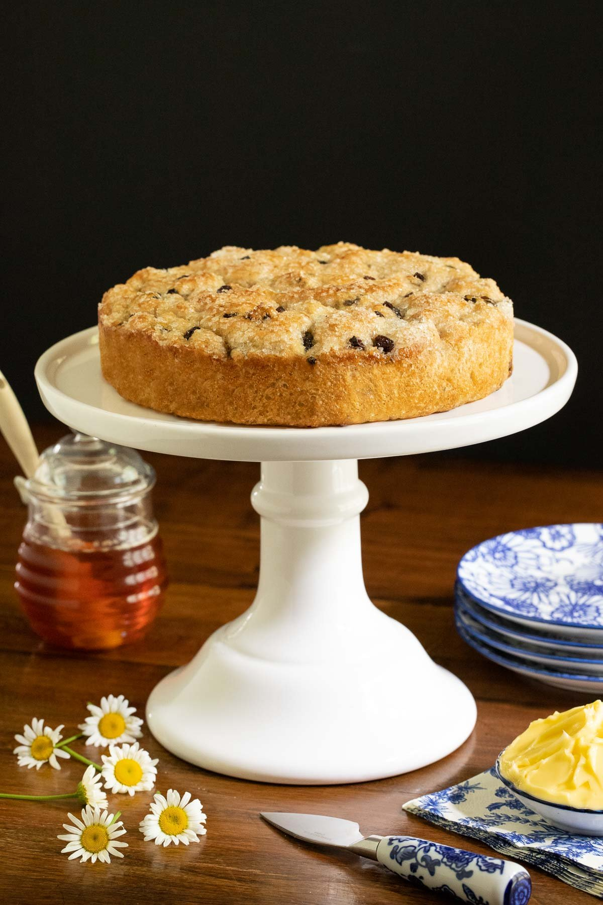 Vertical photo of a loaf of Ridiculously Easy Cinnamon Raisin Focaccia on a white pedestal serving plate.