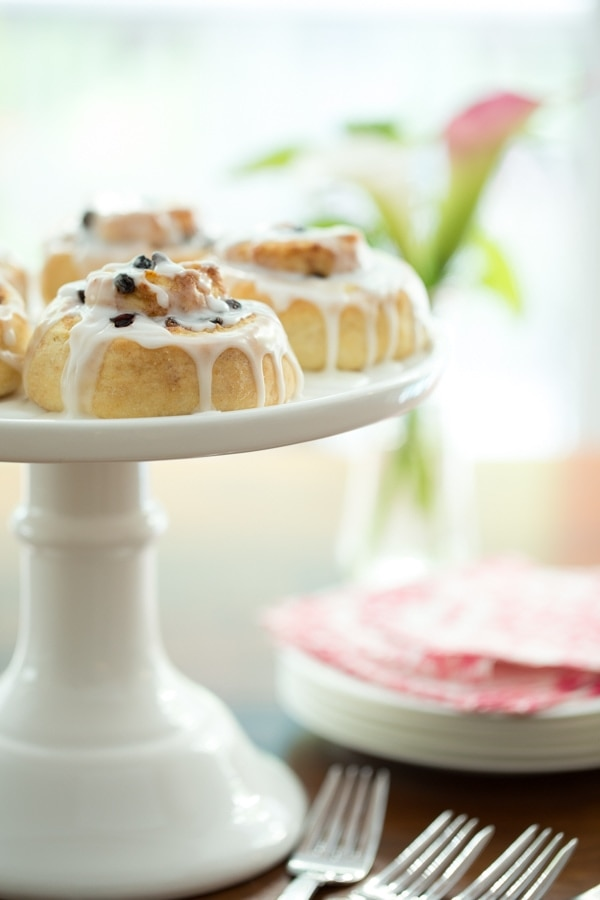 A vertical front shot of a white pedestal cake plate filled with Ridiculously Easy Cinnamon Rolls and plates, forks and napkins beside it.