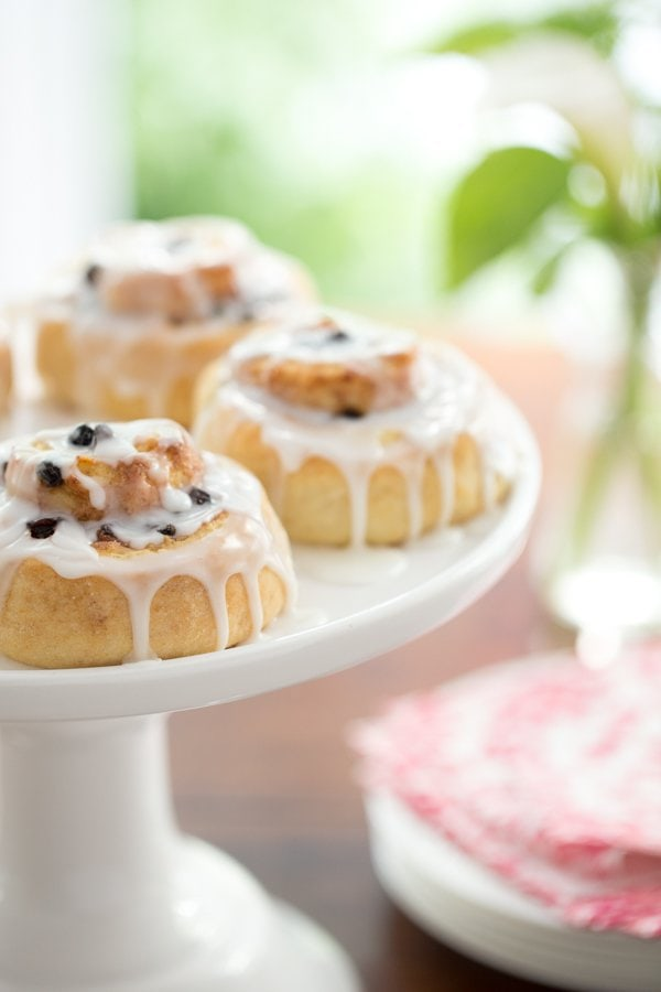 A vertical shot of a white pedestal cake plate filled with Ridiculously Easy Cinnamon Rolls.