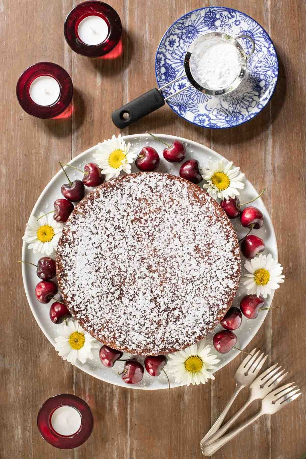 Overhead vertical photo of a Ridiculously Easy Fresh Cherry Almond Cake garnished with fresh daisies and ripe cherries.