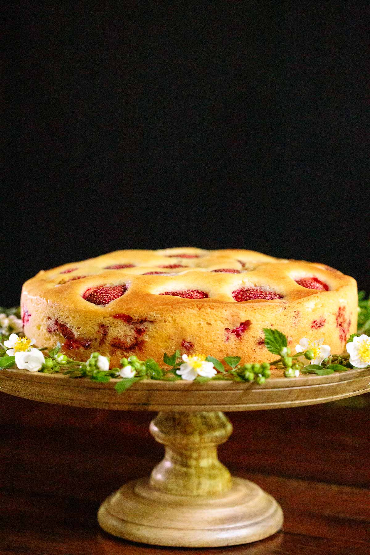 Vertical photo of a Ridiculously Easy Fresh Strawberry Cake on a wood platter against a black background.