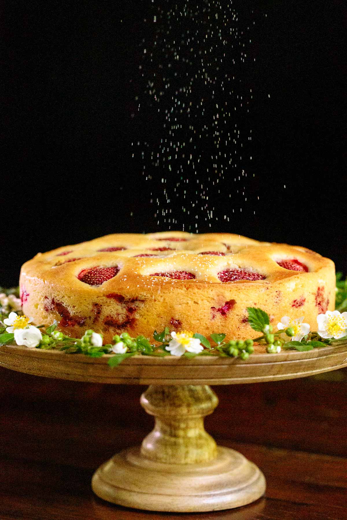 Vertical photo of a Ridiculously Easy Fresh Strawberry Cake on a wood pedestal cake stand with powdered sugar being sprinkled over the top.