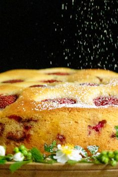 Horizontal closeup photo of a Ridiculously Easy Fresh Strawberry Cake on a wood platter decorated with spring flowers.