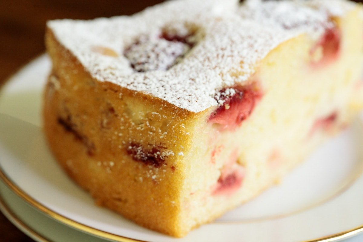 Horizontal extreme closeup of a slice of Ridiculously Easy Fresh Strawberry Cake with powdered sugar on top.
