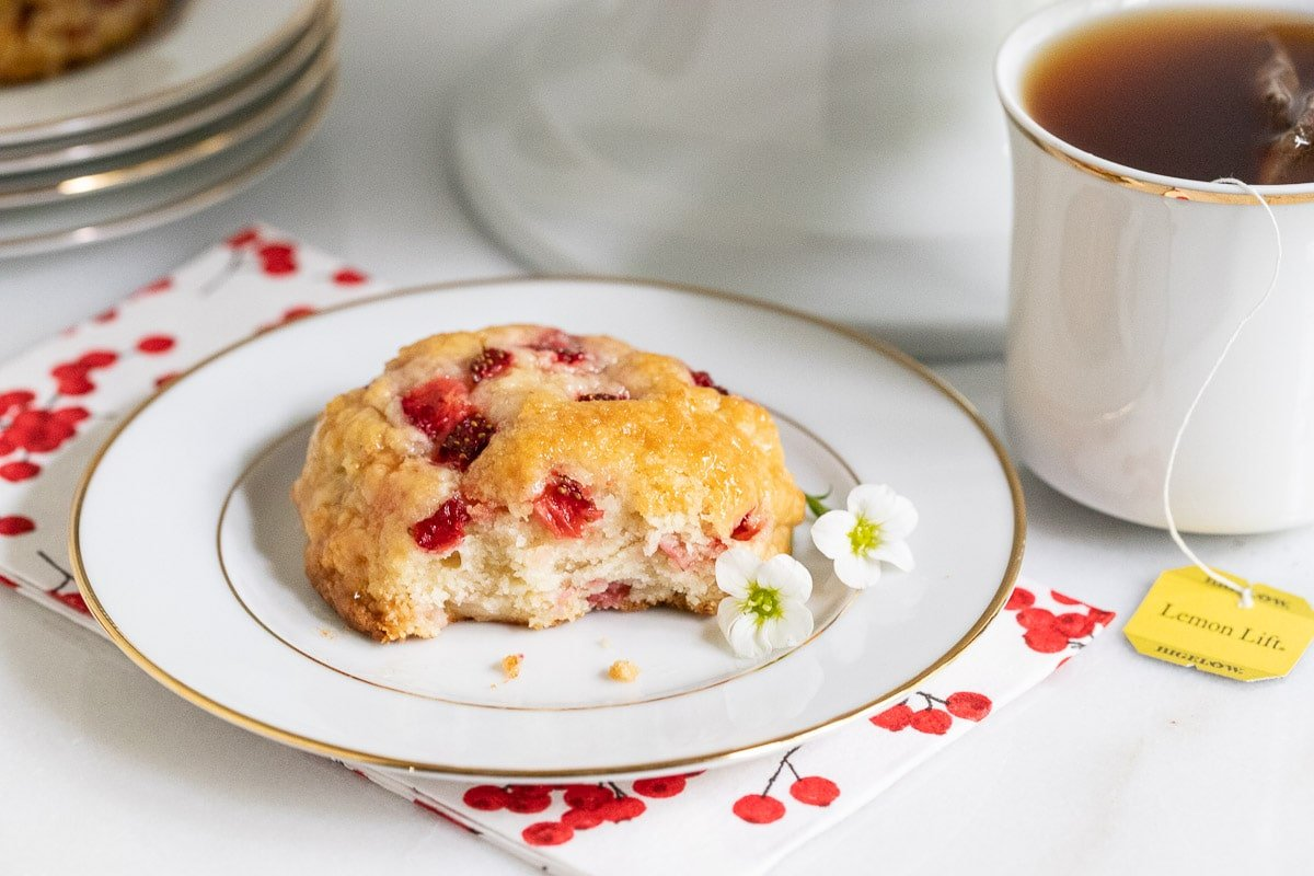 Horizontal picture of a strawberry scone on a white plate and a cup of tea.