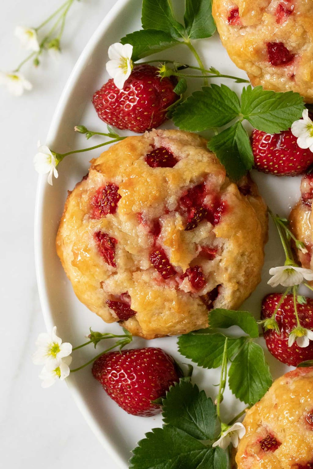 Overhead vertical closeup photo of a platter filled with Ridiculously Easy Fresh Strawberry Scones and decorated with strawberry leaves and flowers.
