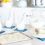Horizontal photo of a Ridiculously Easy Lemon Poppy Seed Sheet Cake on a kitchen countertop with glasses and a pitcher of milk in the background.