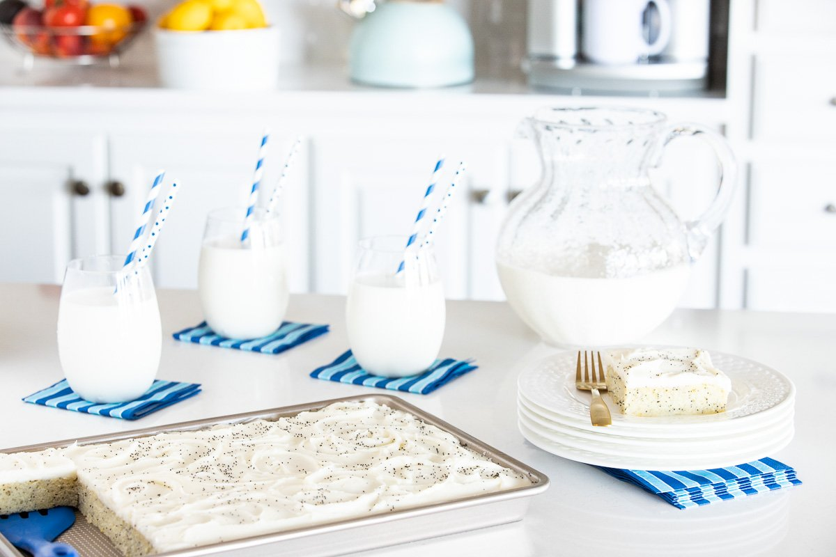 Horizontal photo of a Ridiculously Easy Lemon Poppy Seed Sheet Cake on a kitchen counter with glasses and a pitcher of milk in the background.