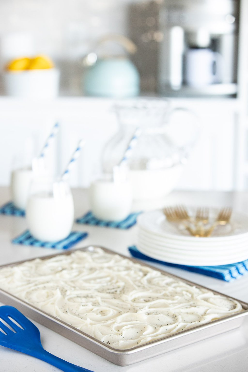 Vertical photo of a Ridiculously Easy Lemon Poppy Seed Sheet Cake on a kitchen countertop with glasses and a pitcher of milk in the background.