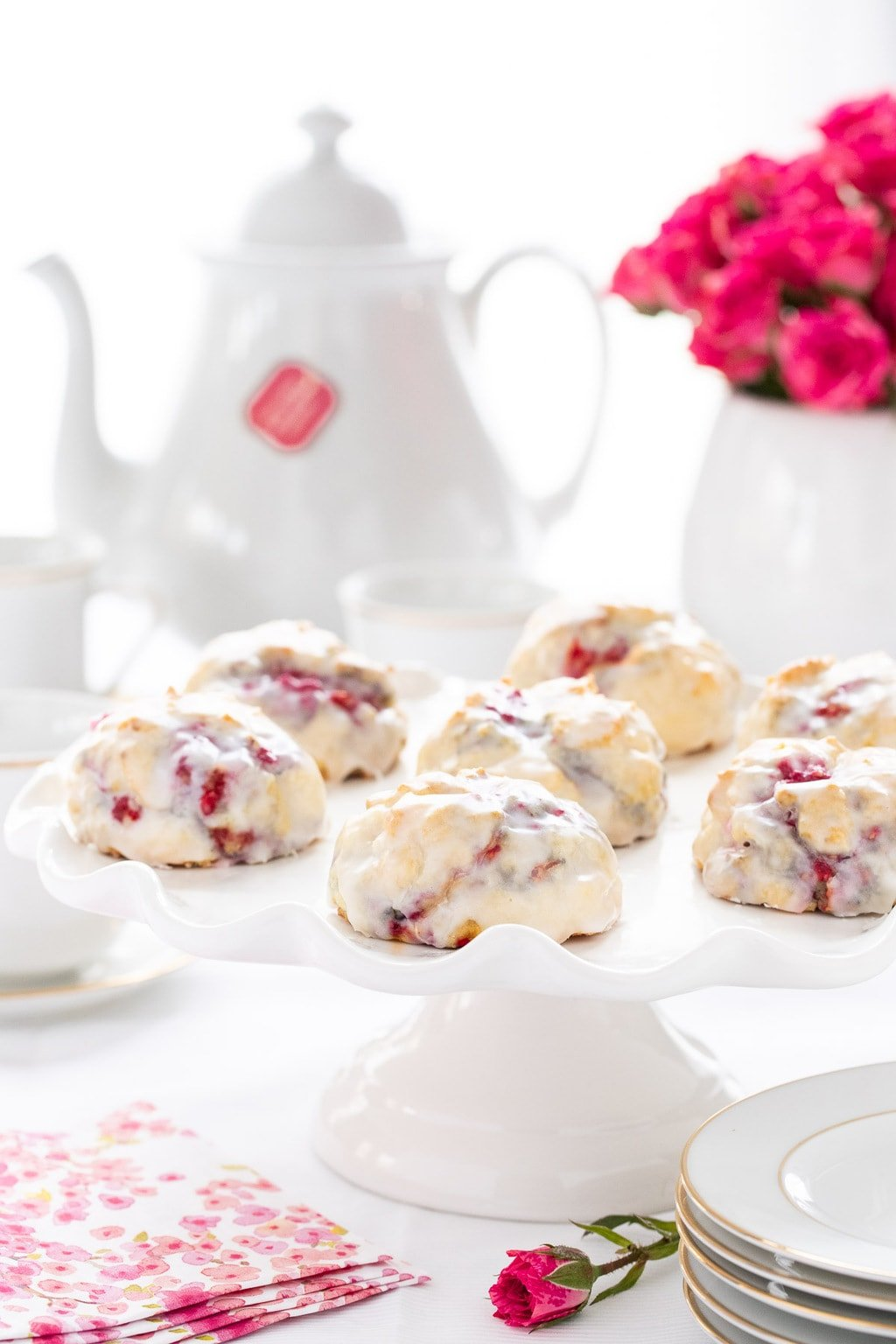 Vertical photo of a serving plate of Ridiculously Easy Lemon Raspberry Scones with a tea pot and vase of flowers in the background.
