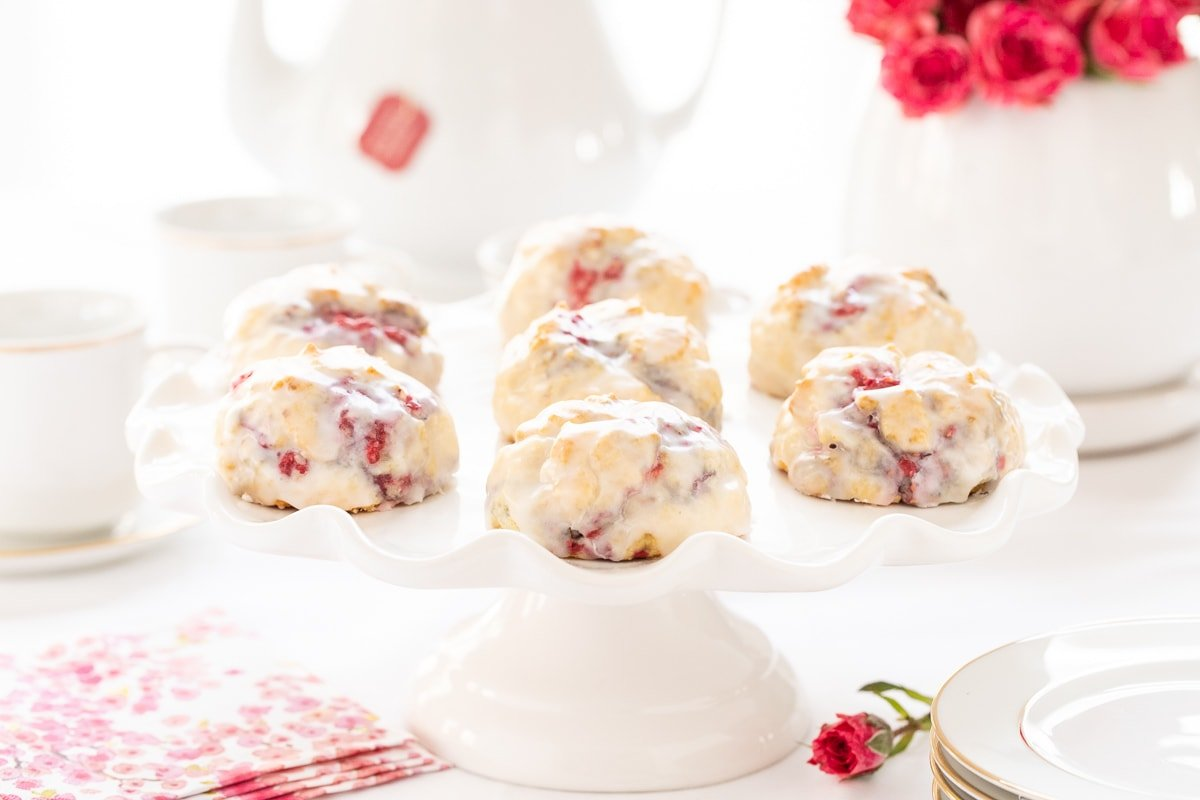 Horizontal photo of a pedestal plate full of Ridiculously Easy Lemon Raspberry Scones.