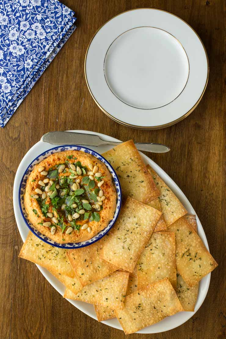 Overhead view of crackers and hummus on a white platter. Holiday appetizers post.
