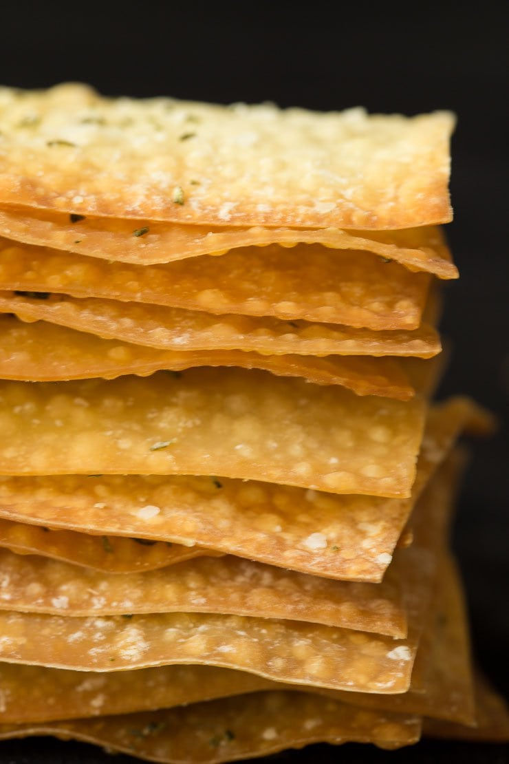 Photo of a stack of Ridiculously Easy Olive Oil Rosemary Crackers showing their thin, crisp edges.