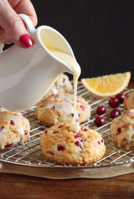 Vertical picture of orange cranberry scones on a cooling rack with glaze drizzled over the top