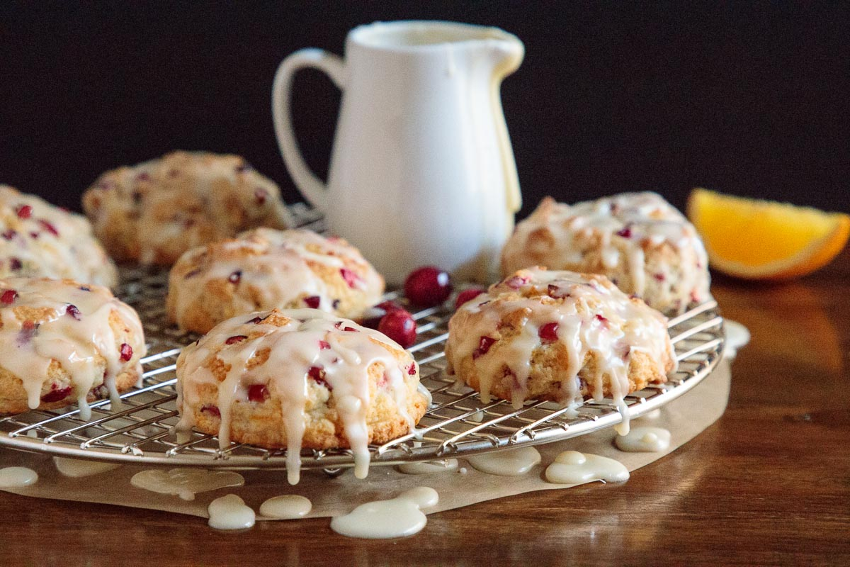 Photo of a batch of Ridiculously Easy Orange Cranberry Scones on a metal cooling rack with parchment paper underneath.