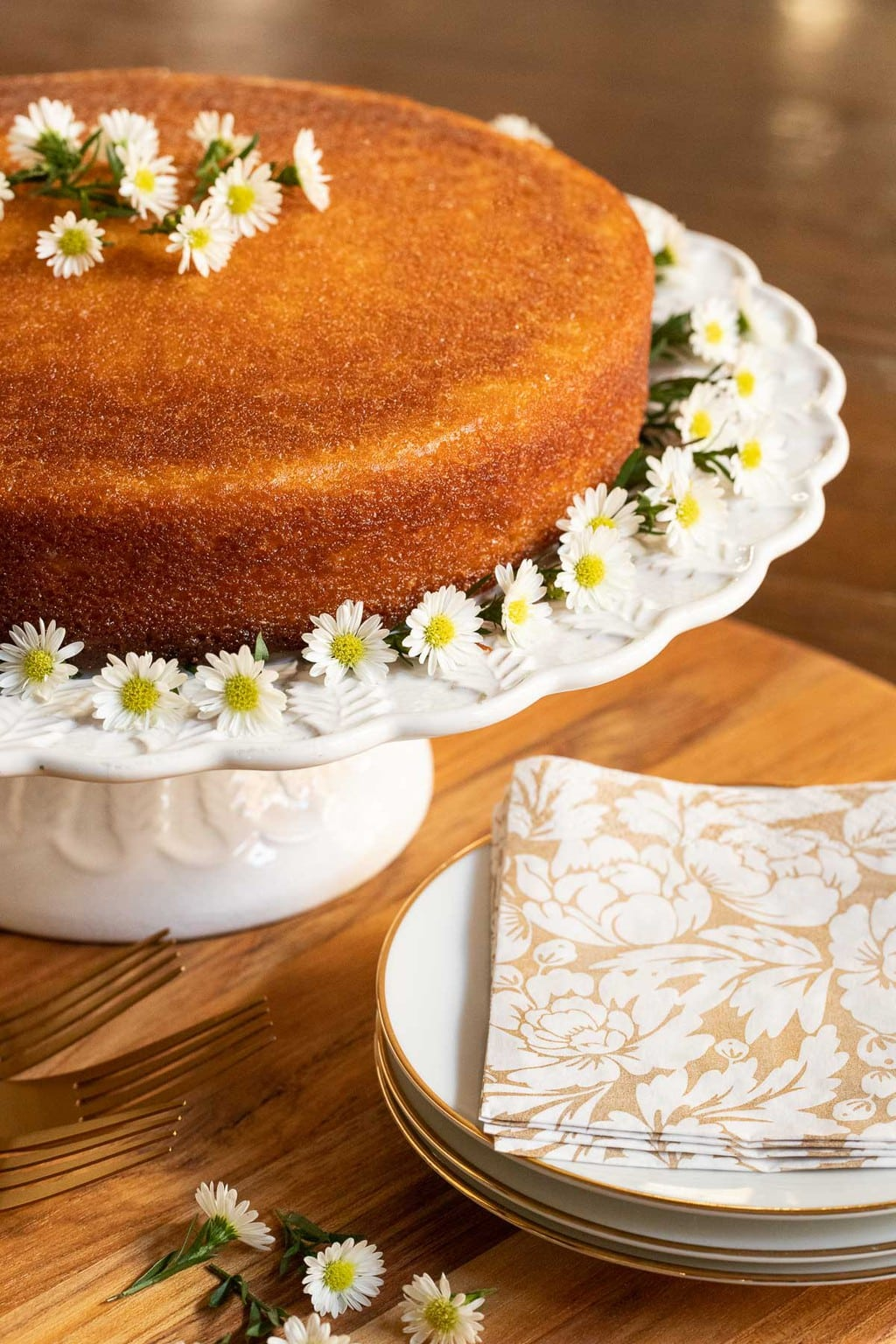 Vertical photo of a Ridiculously Easy Orange Olive Oil Cake on a white scalloped pedestal cake platter and decorated with mini daisies.