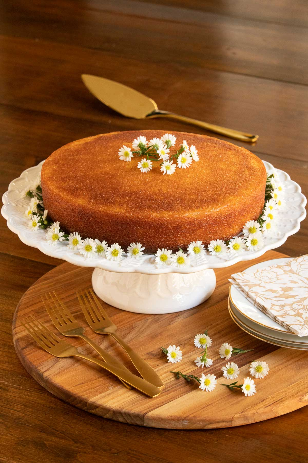 Vertical long photo of a Ridiculously Easy Orange Olive Oil Cake on a white pedestal cake stand decorated with mini daisies.