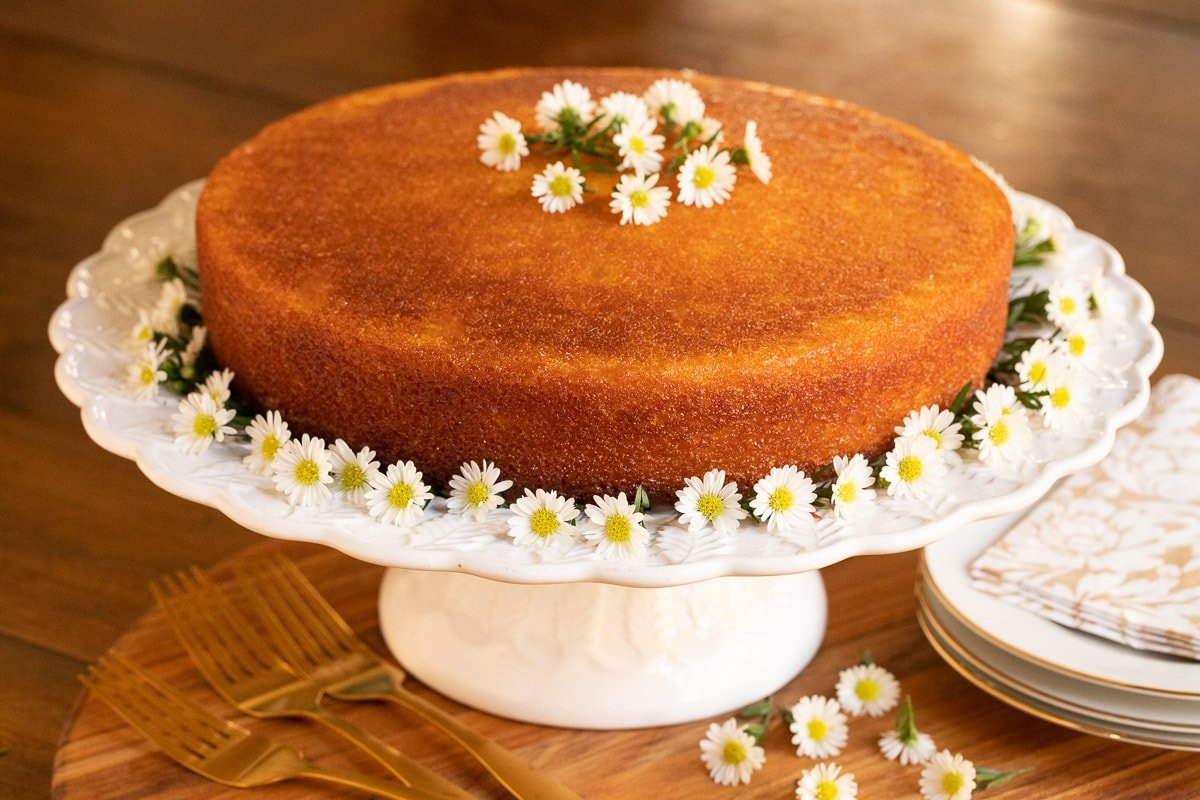 Horizontal photo of a Ridiculously Easy Orange Olive Oil Cake on a white scalloped platter decorated with mini daisies.