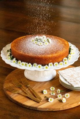 Vertical photo of a Ridiculously Easy Orange Olive Oil Cake on a scalloped pedestal cake stand and decorated with mini daisies.