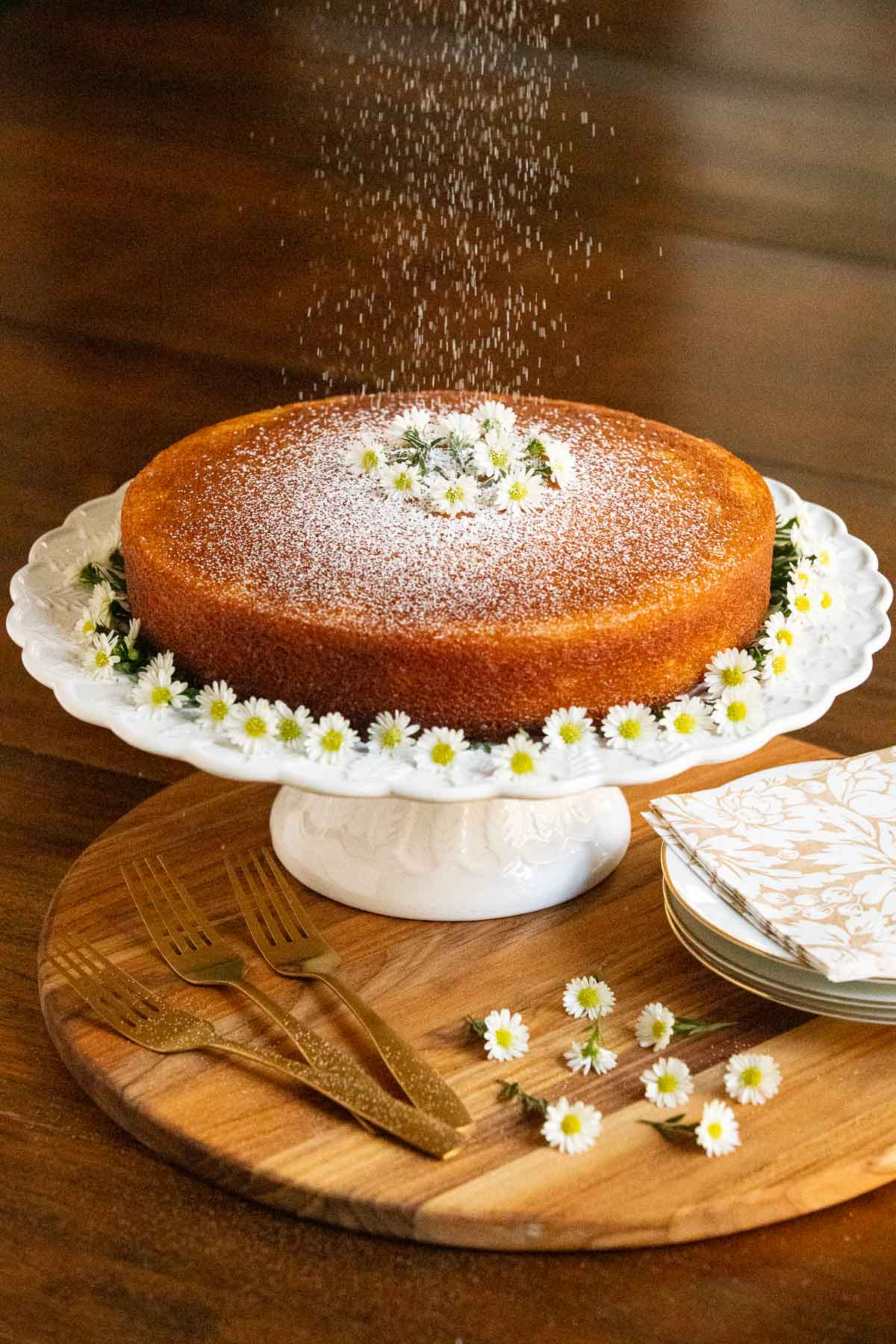Vertical photo of a Ridiculously Easy Orange Olive Oil Cake on a white pedestal cake stand being sprinkled with powdered sugar.