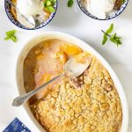 Overhead picture of easy peach crumble scooped into small bowls with ice cream