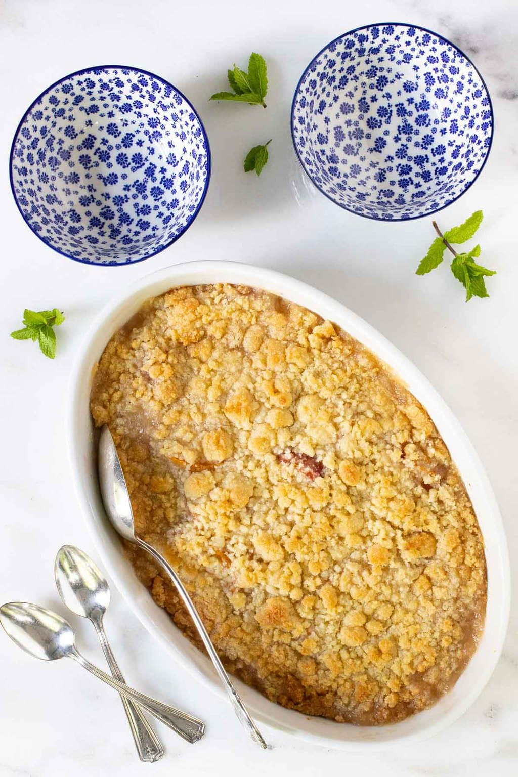 Overhead vertical photo of a Ridiculously Easy Peach Crumble in a white oval serving dish with blue and white patterned individual serving bowls along side.