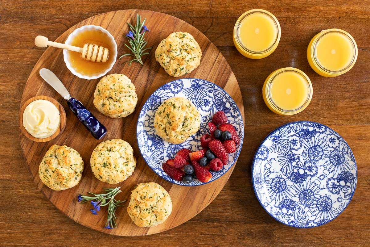 Overhead horizontal photo of a circular wood tray filled with Ridiculously Easy Rosemary Parmesan Biscuits, fresh fruit, butter and honey.