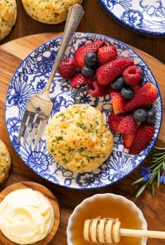 Vertical overhead photo of Ridiculously Easy Rosemary Parmesan Biscuits on a blue and white patterned plate with fresh berries, honey and butter.