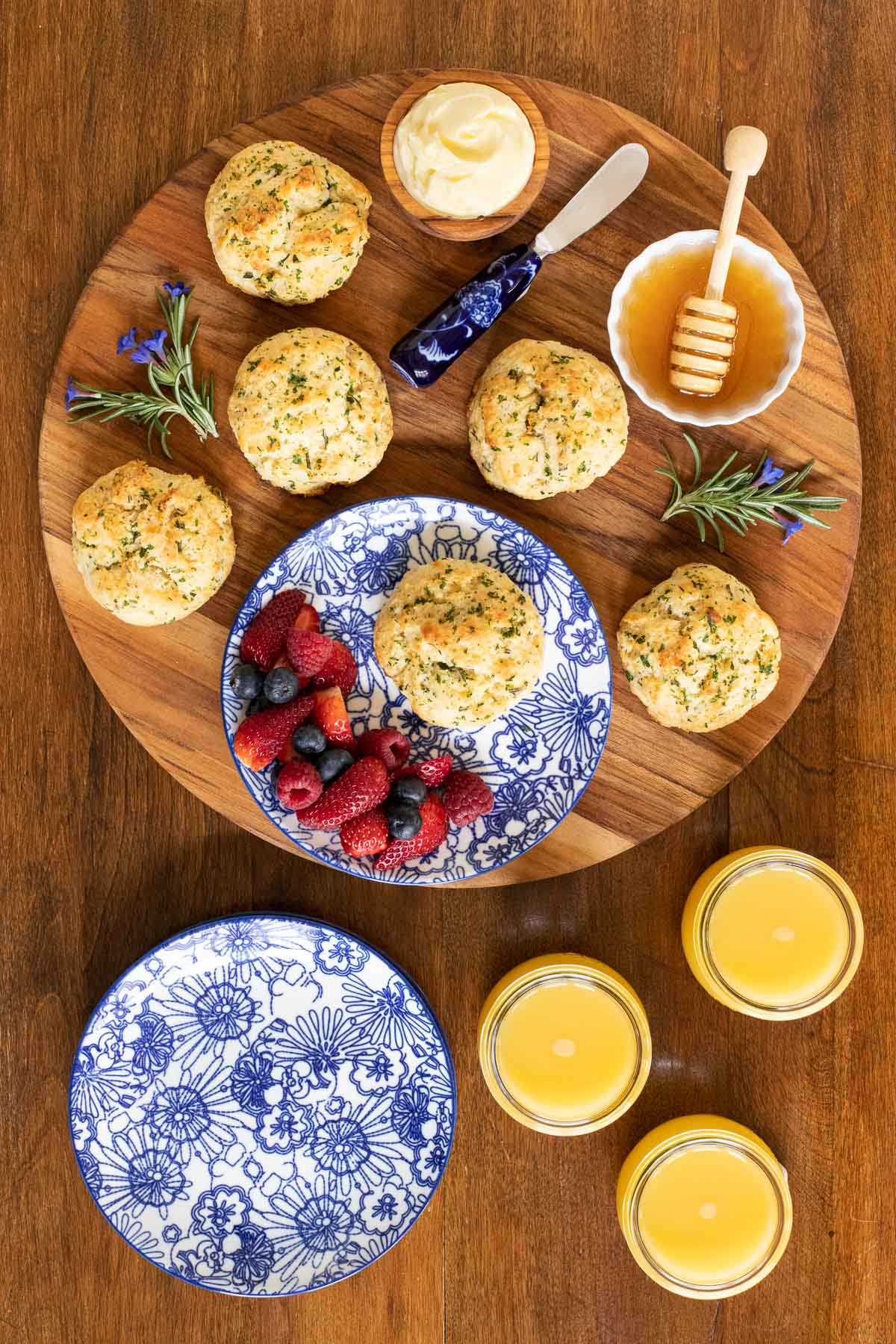 Vertical overhead photo of Ridiculously Easy Rosemary Parmesan Biscuits on a round wood serving platter surrounded by glasses of orange juice, fresh fruit and containers of honey and whipped butter.