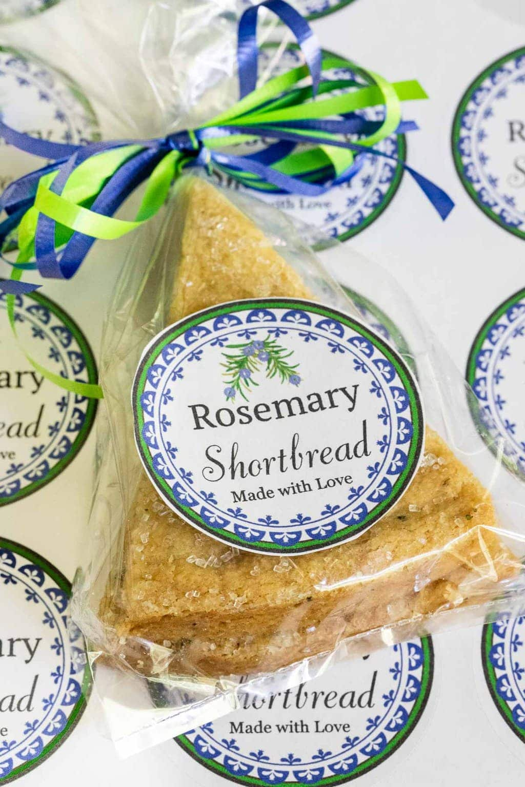Vertical photo of Ridiculously Easy Rosemary Shortbread packaged in clear plastic bags for gift giving. A colorful decorative self adhesive label is on the bag