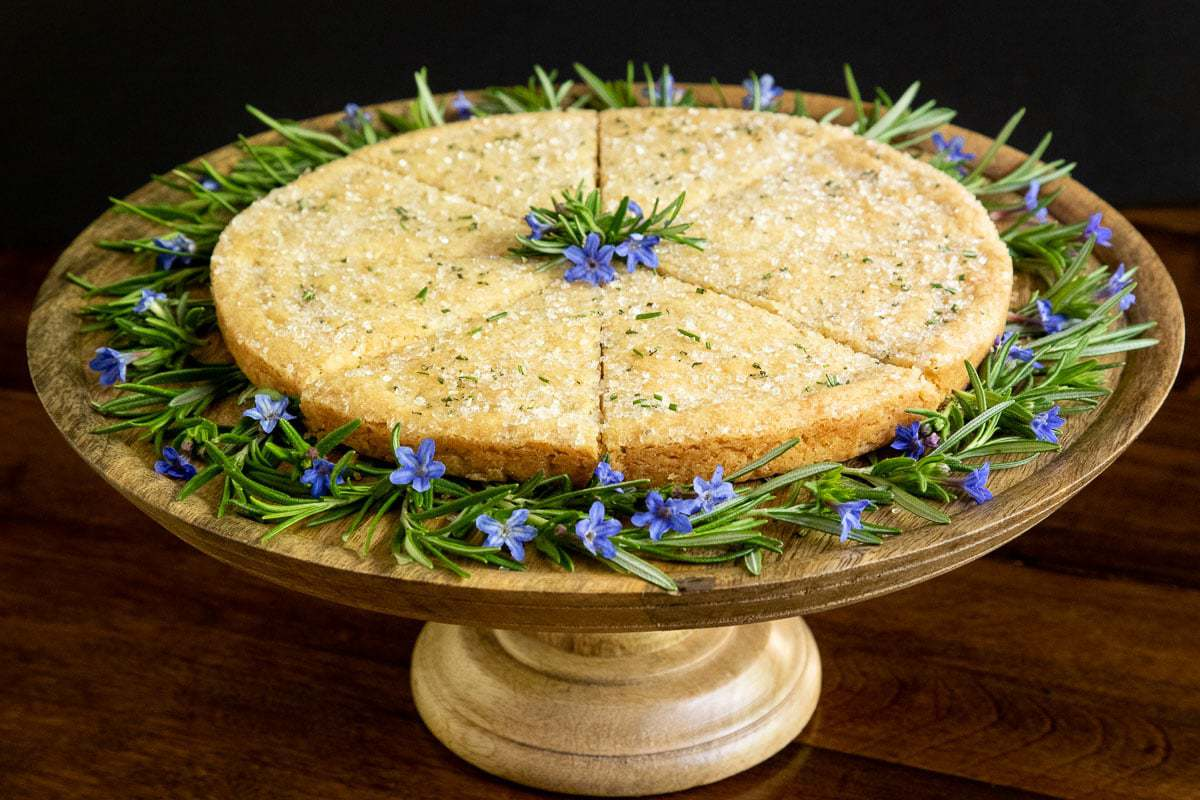 Horizontal photo of a wood pedestal cake stand with Ridiculously Easy Rosemary Shortbread on it decorated with blue and green flowers.