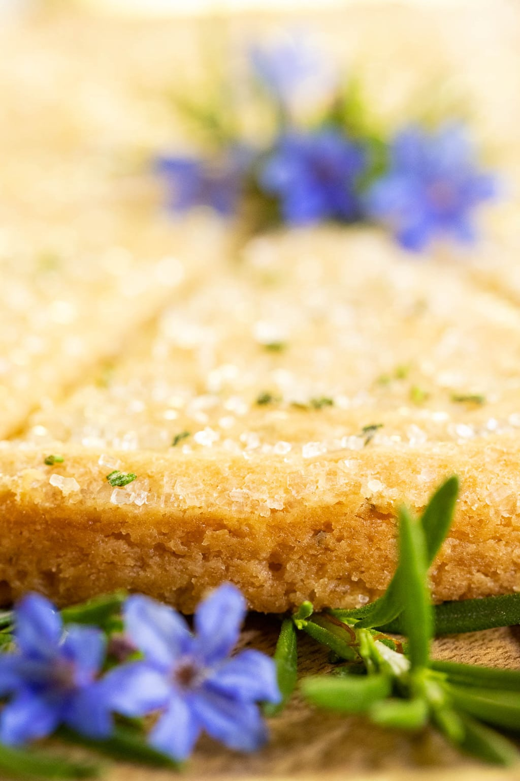 Ultra closeup vertical photo of the edge of Ridiculously Easy Rosemary Shortbread decorated with blue and green flowers.