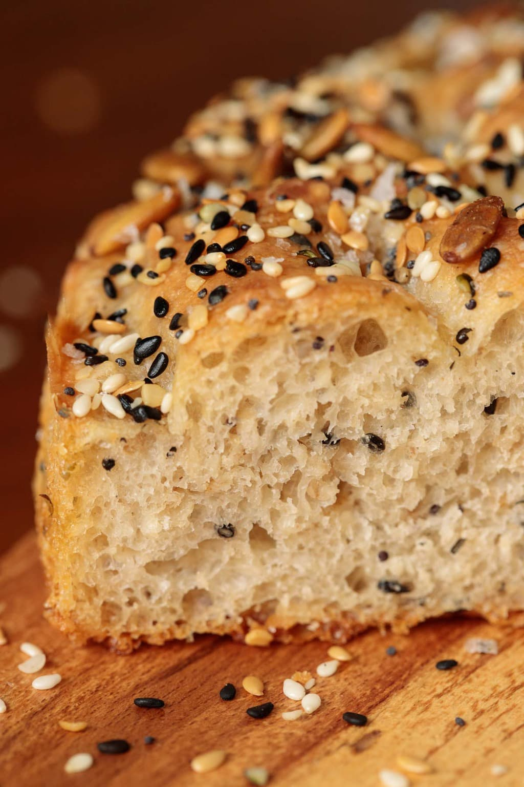 Ultra closeup photo of a slice of Ridiculously Easy Seeded Focaccia Bread resting on a wood cutting board.