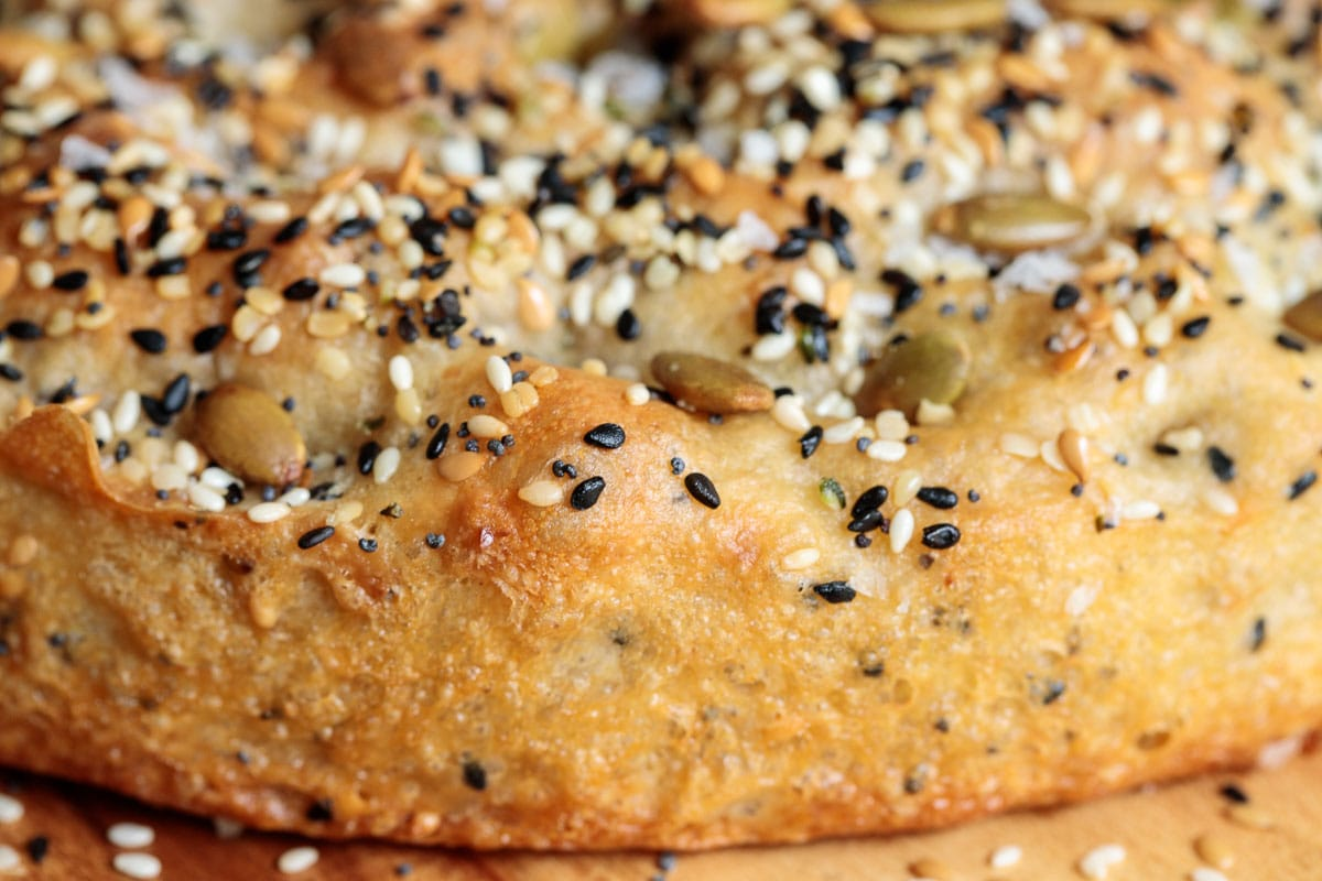 Closeup photo of the side and top of a loaf of Ridiculously Easy Seeded Focaccia Bread.
