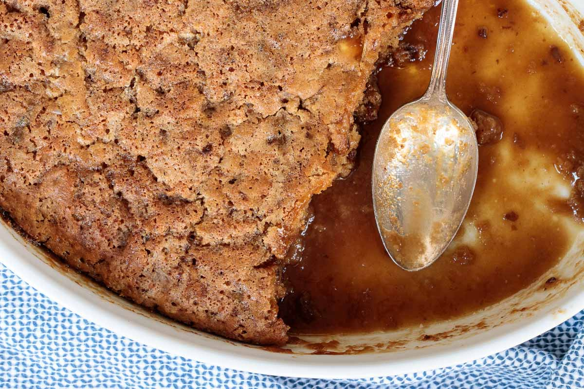 Overhead closeup photo of a white serving dish of Ridiculously Easy Sticky Toffee Pudding featuring the toffee sauce.