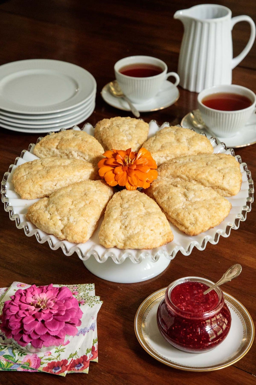 Photo of a plate of Sugar Top Scones surrounded by cups of tea and serving plates.