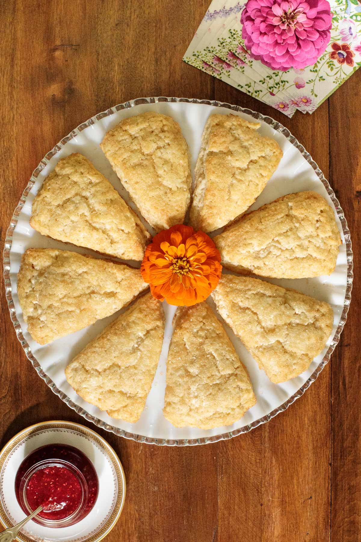Overhead vertical photo of Ridiculously Easy Sugar Topped Scones on a white glass platter on a wood table.