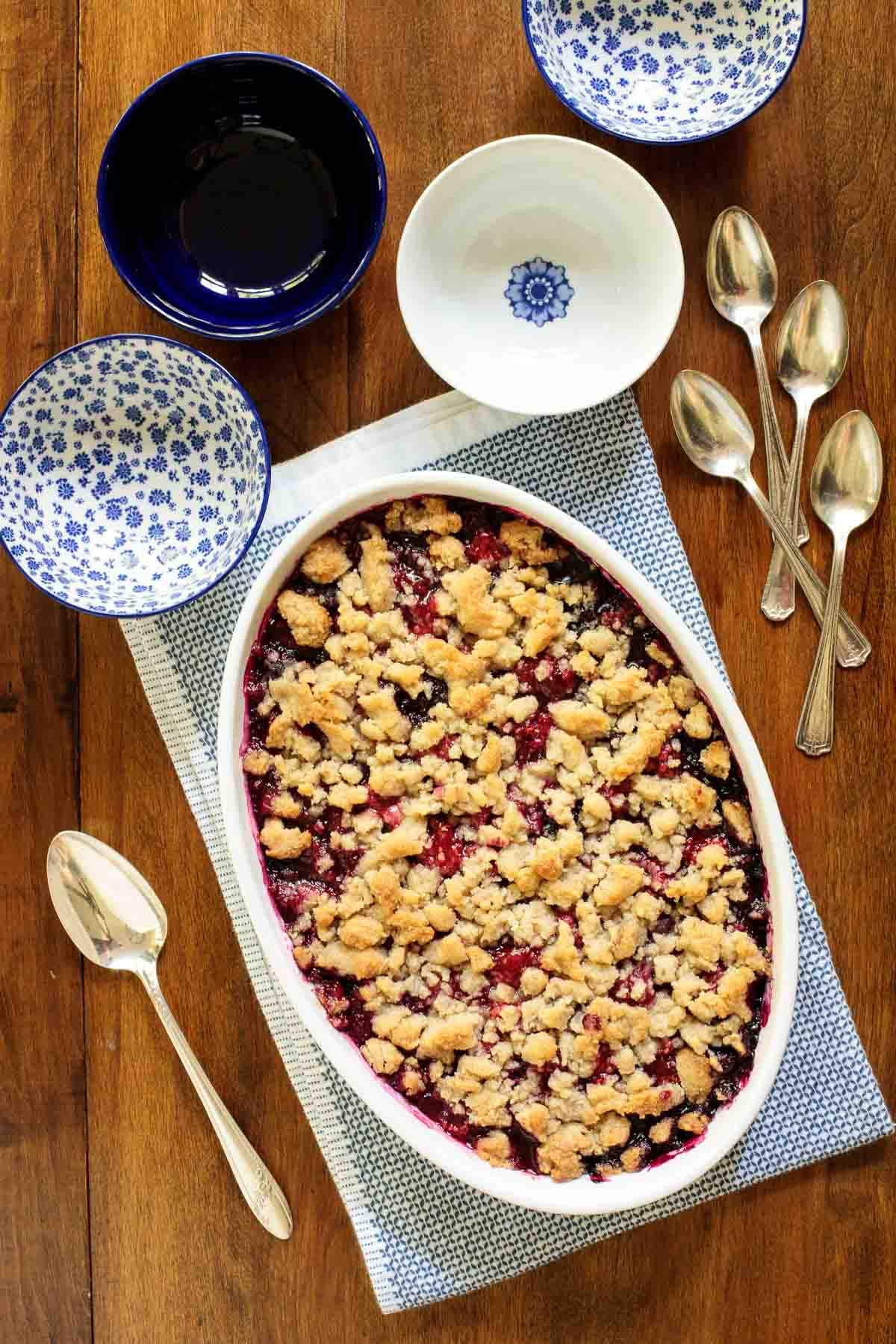 Overhead photo of a Ridiculously Easy Summer Berry Crisp in a white porcelain serving dish surrounded by blue and white patterned individual serving dishes and dessert spoons.