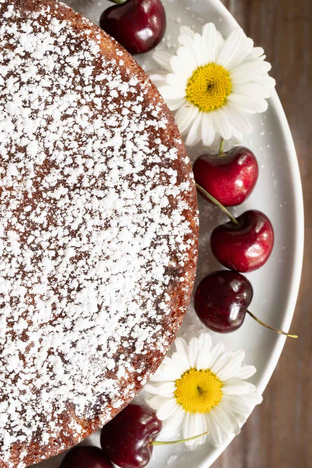 Overhead closeup vertical photo of the powdered sugar dusted top of a Ridiculously Easy Fresh Cherry Almond Cake decorated with fresh whole cherries and daisies.