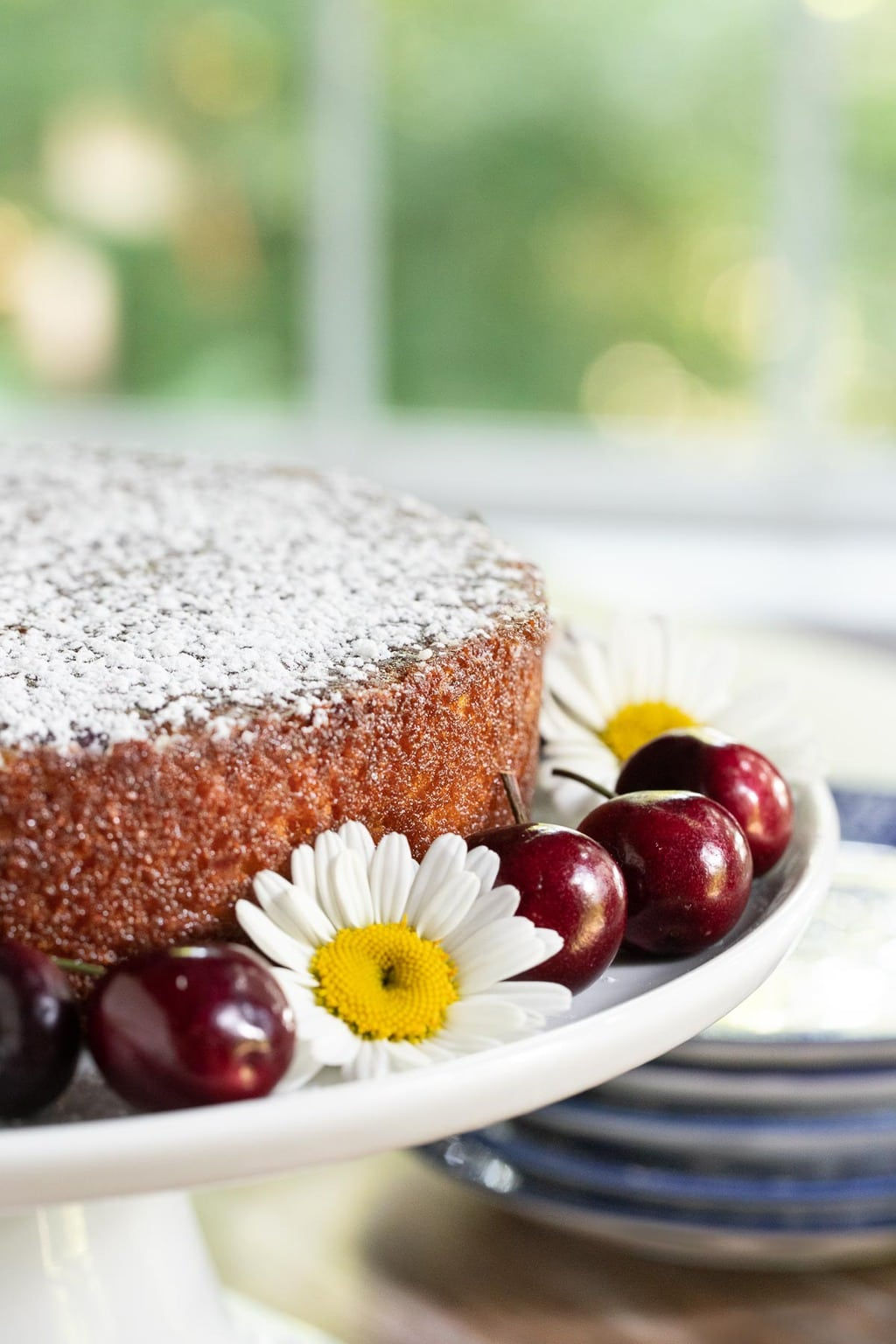 Vertical photo of a Ridiculously Fresh Sweet Cherry Almond Cake with an outdoor scene through a window in the background. The cake is decorated with fresh daisies and cherries.
