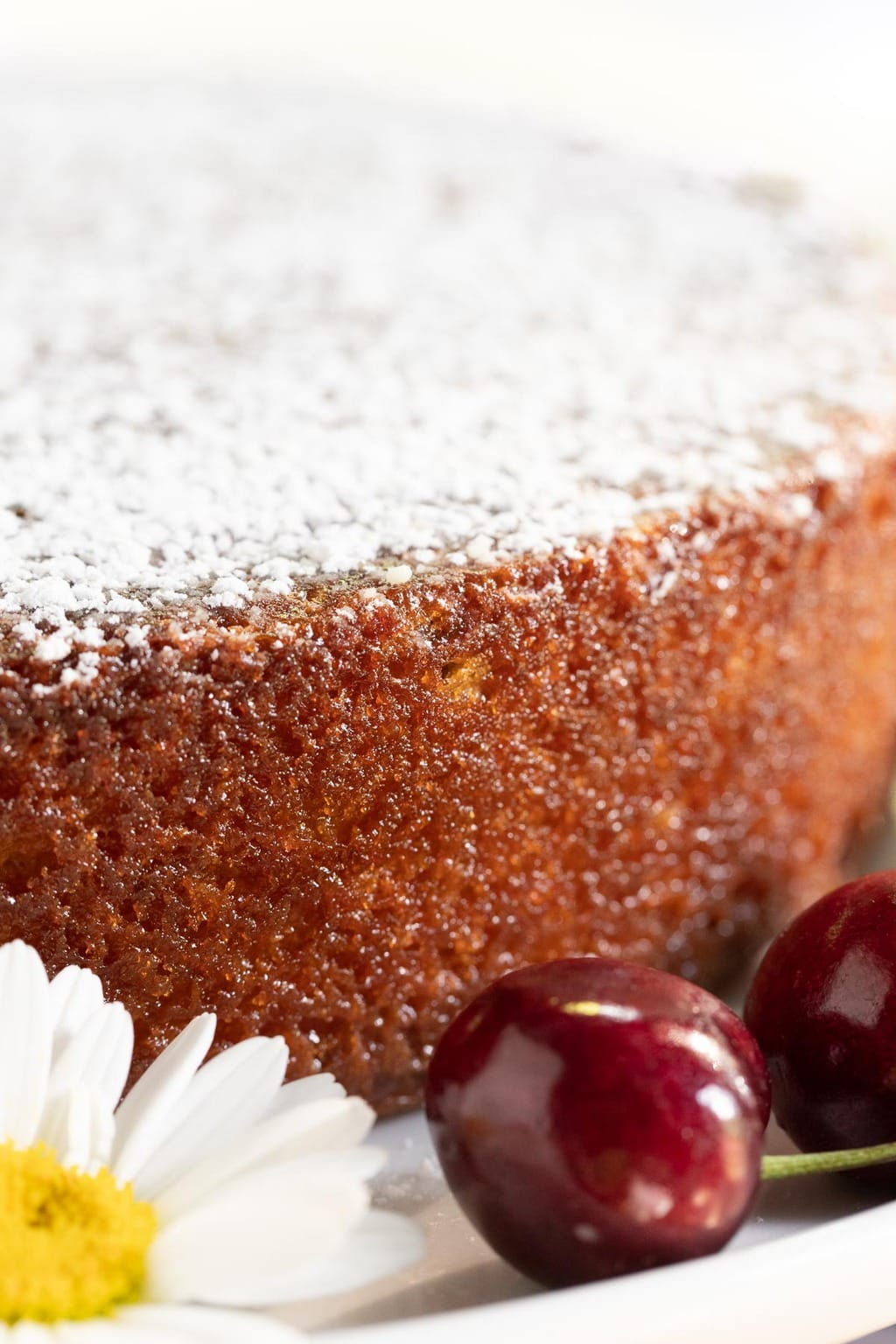 Closeup photo of the side and powdered sugar top of a Ridiculously Easy Sweet Cherry Almond Cake.