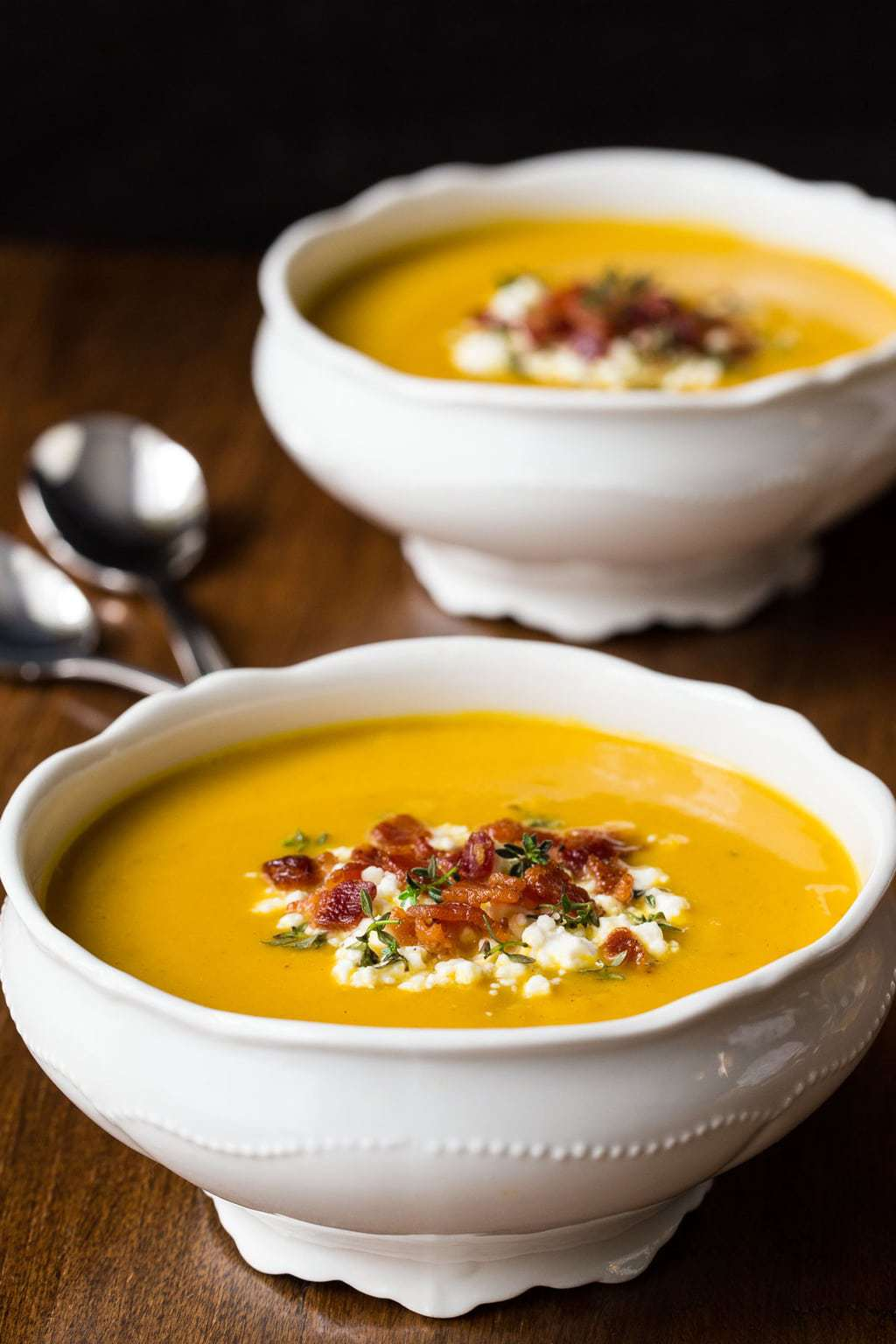 Photo of two white bowls of Roasted Butternut Bacon Soup on a wood table.