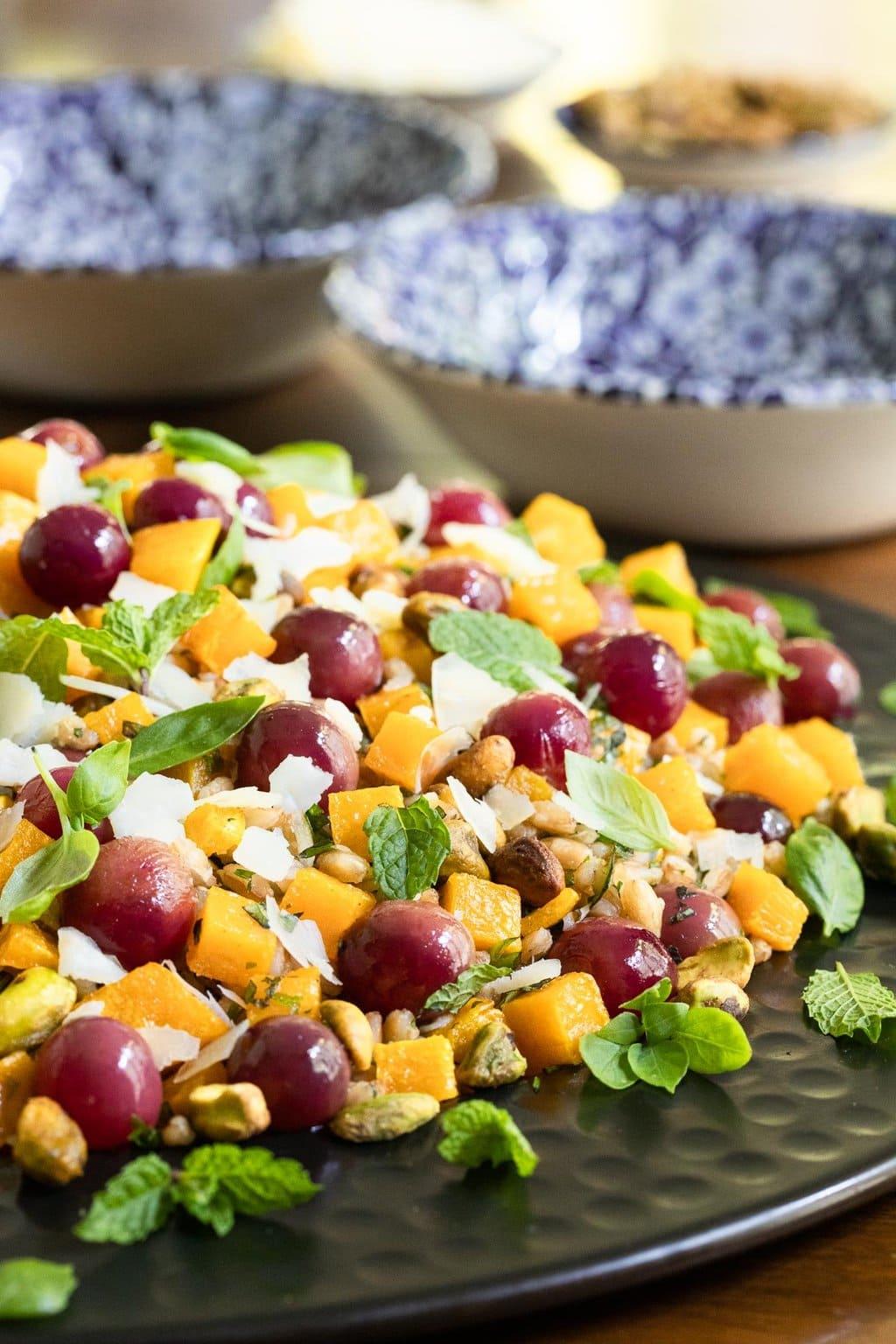 Vertical closeup photo of a black serving platter of Roasted Butternut Farro Salad.