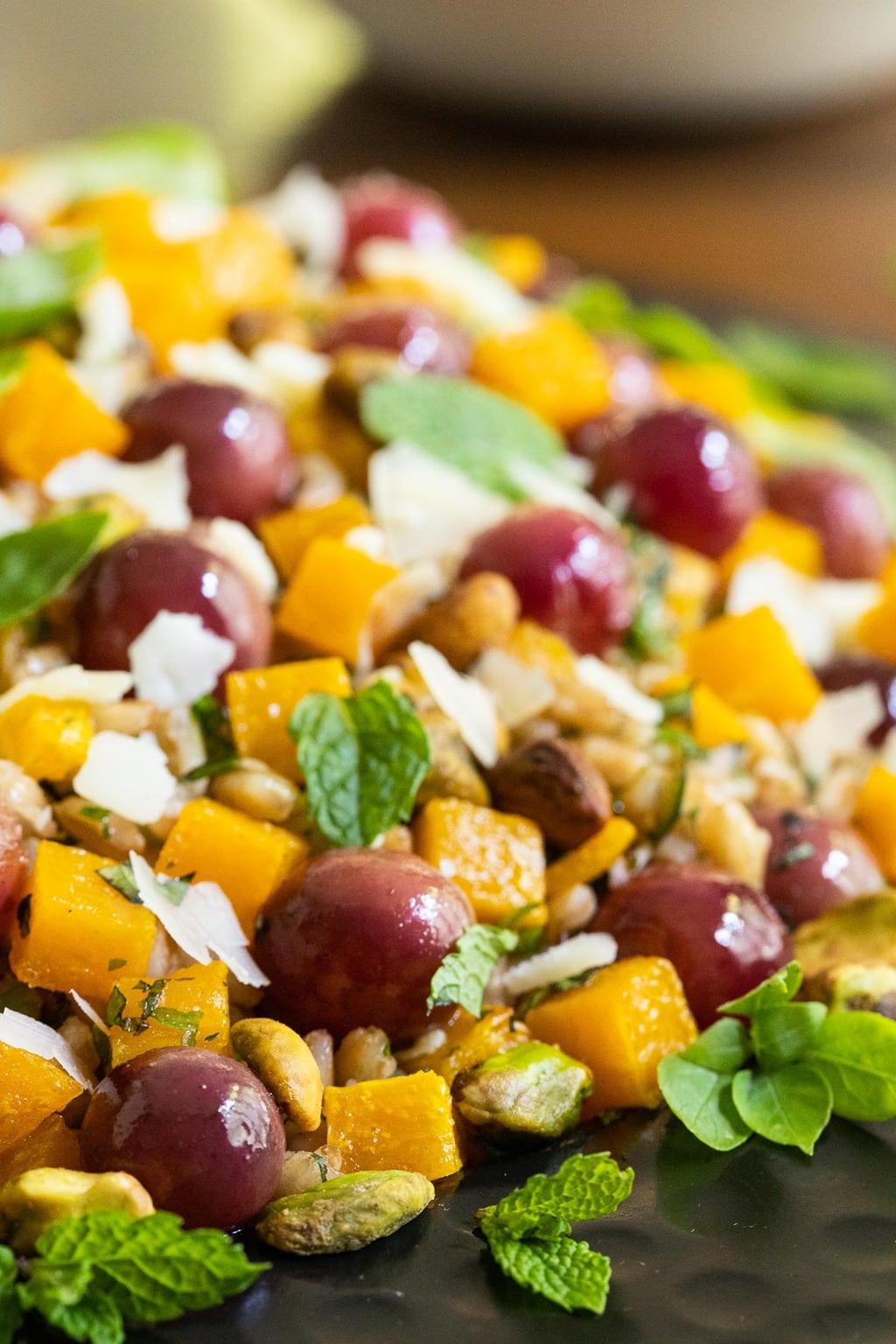 Vertical closeup photo of a platter of Roasted Butternut Farro Salad.