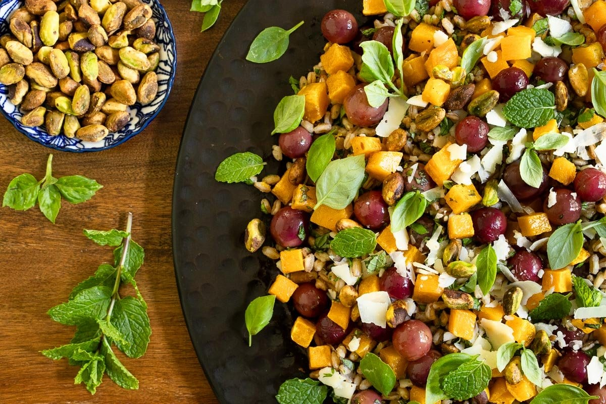 Horizontal closeup photo of a platter of Roasted Butternut Farro Salad with garnishes of fresh mint leaves and a bowl of pistachios nearby.