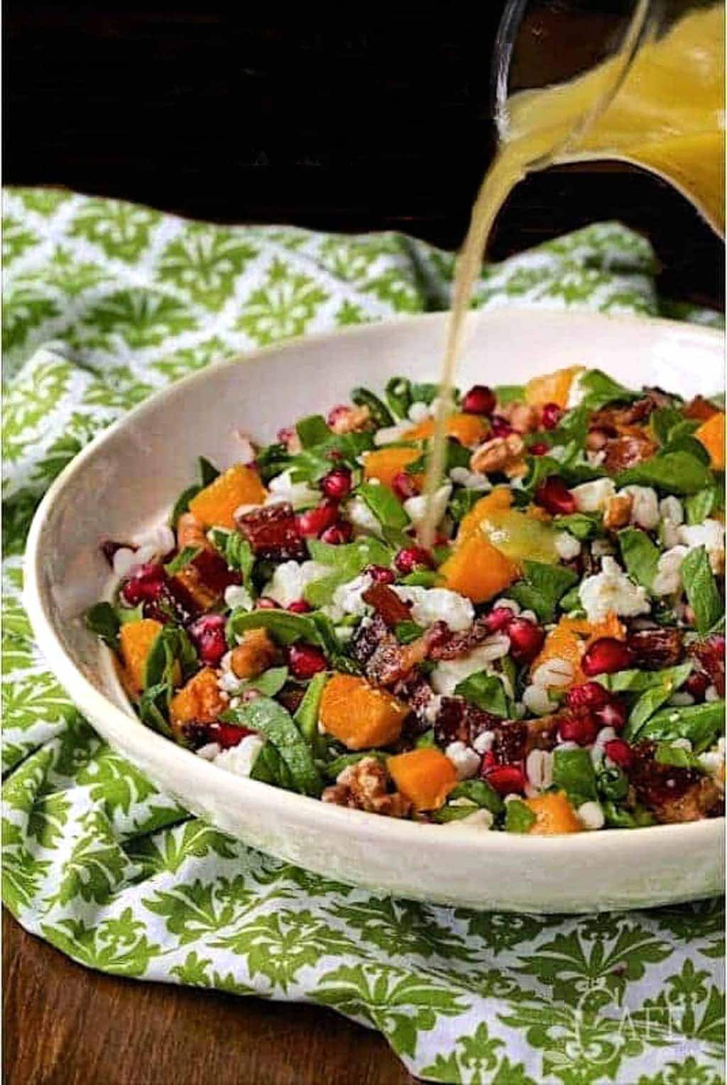 Photo of a white serving bowl filled with Roasted Butternut Salad on a white and green patterned napkin.