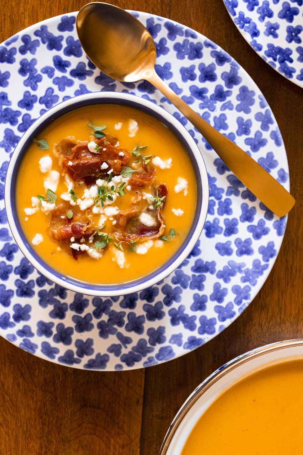Overhead vertical closeup photo of Roasted Butternut Squash Soup with crispy pancetta and feta cheese on top on a blue and white patterned plate and bowl.
